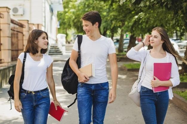 alegre-estudiantes-caminando-parque_23-2147656235